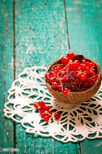 904734850istockphoto Fresh red currant on wooden table 490725502