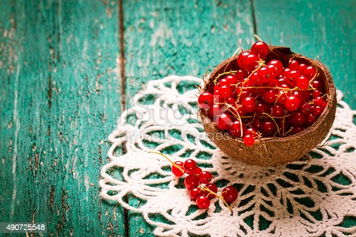 904734850istockphoto Fresh red currant on wooden table 490725548