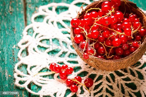 904734850istockphoto Fresh red currant on wooden table 490725590