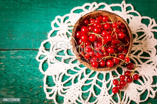 904734850istockphoto Fresh red currant on wooden table 490725636