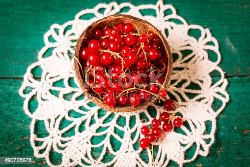 904734850istockphoto Fresh red currant on wooden table 490725678