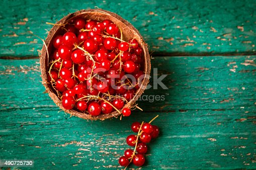904734850istockphoto Fresh red currant on wooden table 490725730