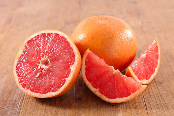 fresh red grapefruit - grapefruit stock photos and pictures