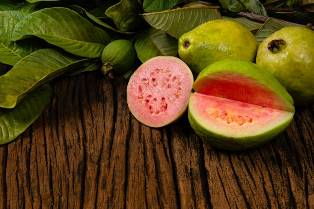 Fresh red guavas with green leaves on wooden demolition background. Wood texture and guava leaves Fresh red guavas with green leaves on wooden demolition background. Wood texture and guava leaves. guava stock pictures, royalty-free photos & images