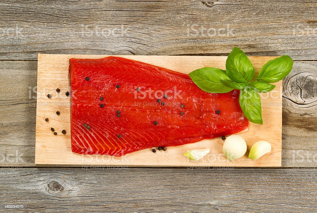Fresh red salmon fillet on cedar cooking plank stock photo