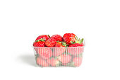 Fresh red strawberries in a plastic transparent container on white background