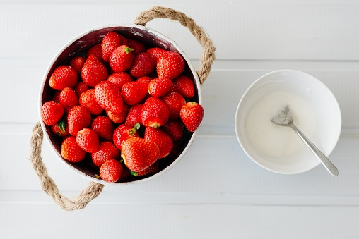 Fresh red strawberries in white bowl and sugarbowl
