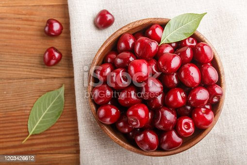 Fresh red sweet cherry in wooden bowl on wooden background. top view, flat lay, close up.