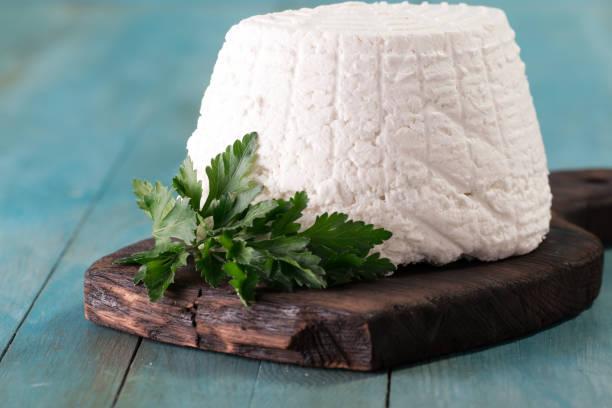 ein frischer ricotta-käse mit petersilie-blatt auf holztisch, italienische küche - ricotta stock-fotos und bilder