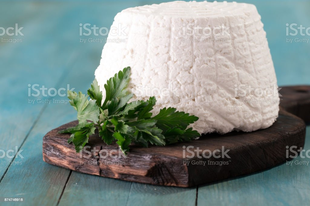 A fresh ricotta cheese with parsley leaf on wooden table, italian food stock photo