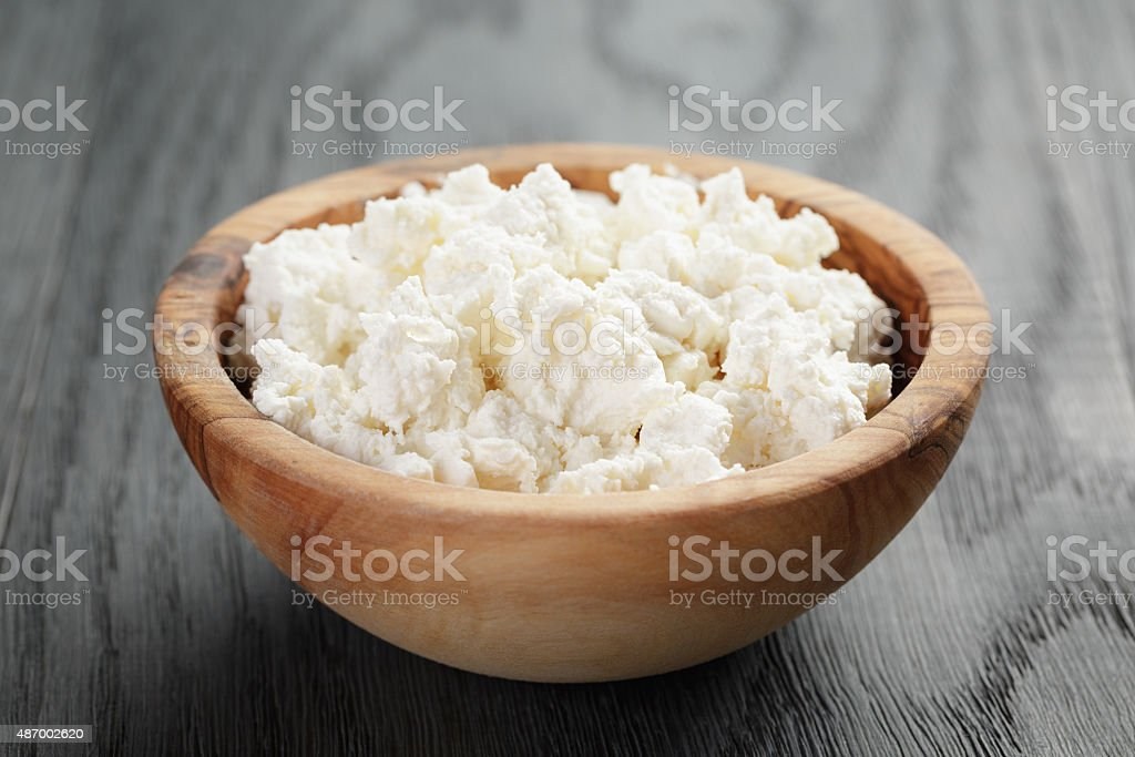fresh ricotta in olive wood bowl on old table stock photo