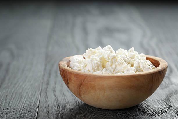 frischer ricotta in olive wood bowl auf alten tisch - ricotta stock-fotos und bilder