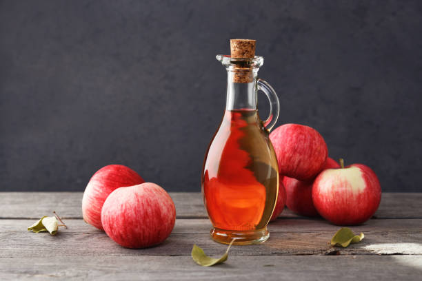Fresh ripe apples and apple cider vinegar on an old wooden table. Dark background. stock photo