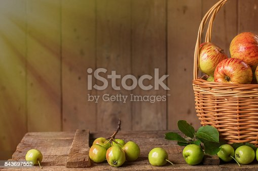 1020586746istockphoto Fresh ripe apples in basket on vintage wood table 843697552