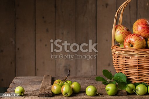 1020586746istockphoto Fresh ripe apples in basket on vintage wood table 844329112