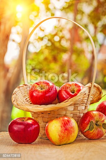 istock fresh ripe apples in wicker busket and on wooden 524472815