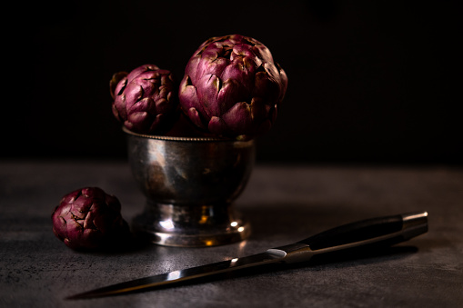 Purple artichoke in a black small silver bowl, place for text on the side. Dark photography style.