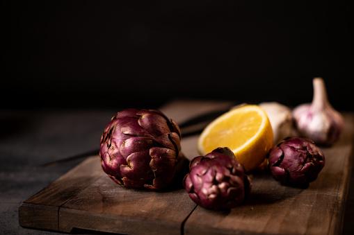Three purple artichoke on the wooden cutting board with lemon and garlic. Dark photography style.