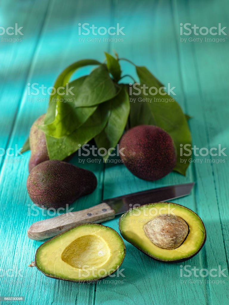 Fresh ripe avocado cut in half next to a cutting knife, on an old wooden turquoise coloured table, with avocados and avocado leaves in the background. royalty-free 스톡 사진