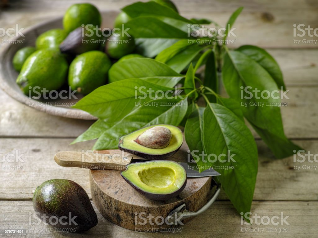 Fresh ripe avocado cut in half on a wooden cutting board on an old wooden table, with a bowl of ripe and unripe avocados in the background. stock photo