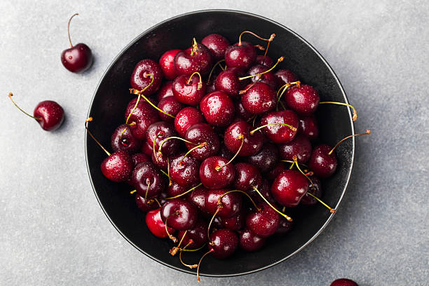 Fresh ripe black cherries in a black bowl Top view stock photo