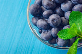 Beautiful fresh blueberries in a glass bowl on a blue background