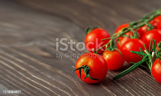 Fresh ripe cherry tomatoes and rosemary branch on dark rustic wooden surface with natural light, close up, copy space for text.