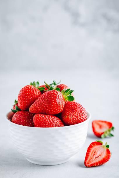 Frisch reife leckere Erdbeere in einer weißen Schüssel auf grauem Steinhintergrund – Foto