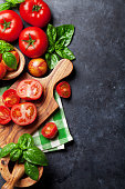 istock Fresh ripe garden tomatoes and basil on stone table 599898994