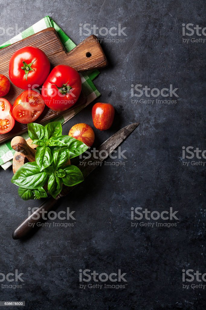 Fresh ripe garden tomatoes and basil on stone table stock photo
