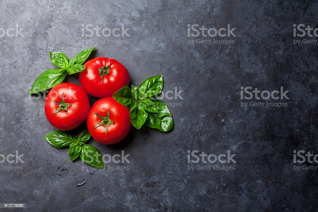 Fresh ripe garden tomatoes and basil stock photo