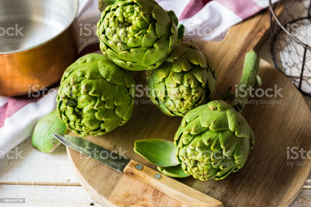 Fresh ripe green artichokes on cutting board, knife, copper dipper in the background, kitchen table, soft day light stock photo