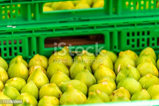 Fresh ripe green yellow color figs fruit in Chiusi, Italy summer street farmer's market display in crates boxes