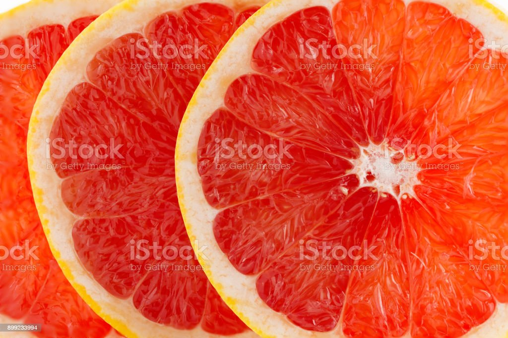 A fresh ripe juicy and appetizing grapefruit and its parts close-up, isolated on a white background stock photo