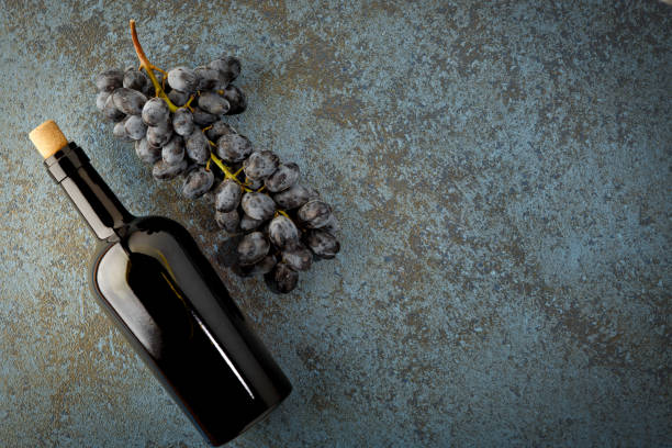 Fresh ripe juicy grapes, bottle of red wine and space for text on top view stock photo