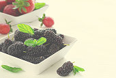 Fresh ripe mulberries and strawberries with mint in bowl on white background, copy space. Horizontal, toned