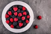 fresh ripe organic raspberries and blackberries in a bowl on a gray rustic background