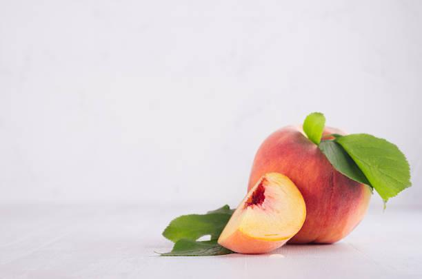 frische reifer pfirsich mit saftigen stück und grünes blatt auf weißen holzplatte, textfreiraum. - tropfenblatt tisch stock-fotos und bilder