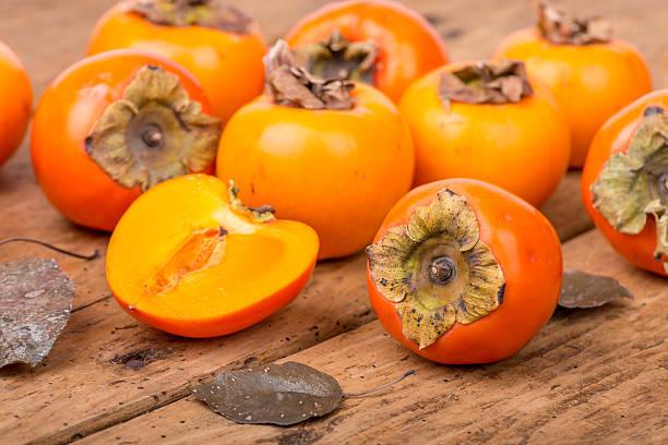 frisch reif persimmon auf einem holztisch-geringe tiefenschärfe - sharonfrucht stock-fotos und bilder
