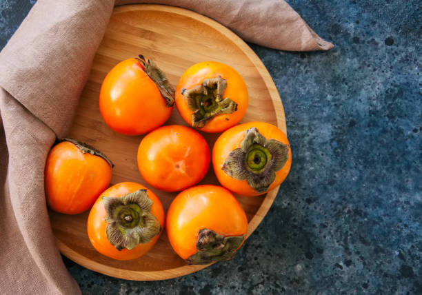 fresh ripe persimmons on a wooden plate on a blue stone background - diospiro imagens e fotografias de stock