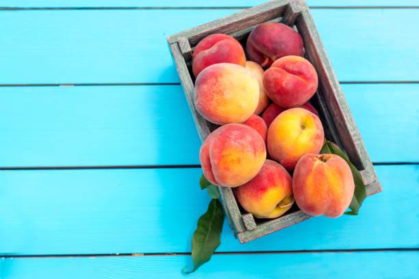 frische reife gepflückten aprikosen in einer holzkiste auf einem blauen tisch im garten. - peach stock-fotos und bilder