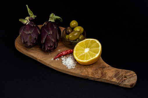 Uncooked whole organic purple artichokes with salt, red pepper, green olives and a halved lemon on a wooden cutting board. Rustic style on black background. Dark photography style with copy space
