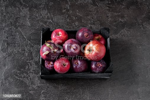 1020586746istockphoto Fresh ripe red apples in the wooden box 1050850822