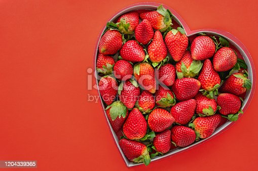 Heart shaped box of strawberries close up on red background