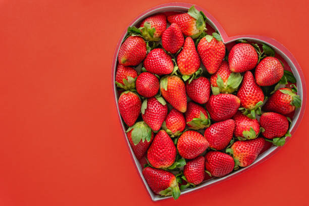 Fresh ripe strawberries in heart shaped box on red background with copy space, view from above stock photo