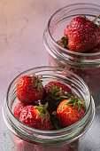 Fresh ripe strawberry fruits in two glass jars, summer vitamin berries on grey stone background, angle view
