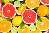 Fresh ripe sweet citrus fruits colorful background: orange, grapefruit, lime, lemon