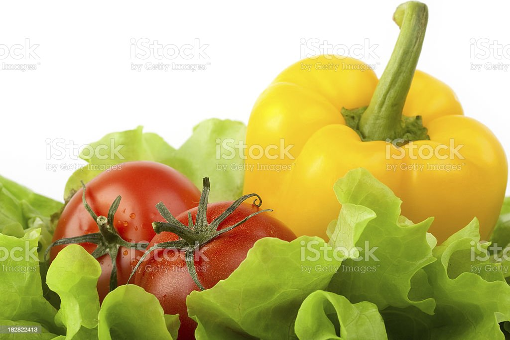 Fresh ripe tomatoes and a pepper over green salad royalty-free stock photo