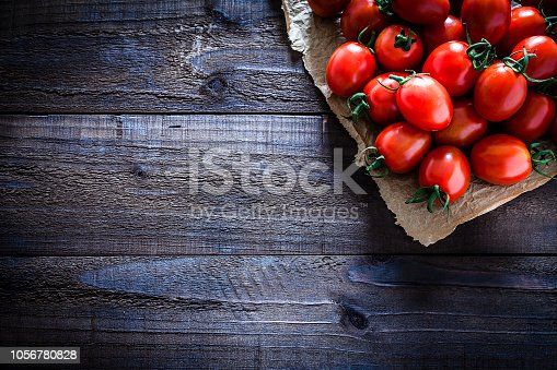 Fresh organic ripe tomatoes on crumpled brown paper arranged at the top-right corner of an old weathered wooden table. Useful copy space left for text and/or logo. Predominant colors are red and brown. Low key DSRL studio photo taken with Canon EOS 5D Mk II and Canon EF 100mm f/2.8L Macro IS USM.