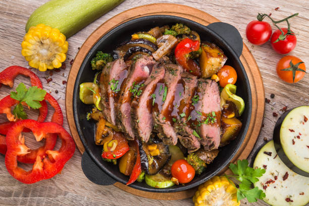 Fresh roast beef on a metal pan Fresh roast beef on a metal pan with vegetables on a wooden table roast beef stock pictures, royalty-free photos & images